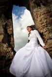 Braut, die auf Ruinen sitzt Stockfoto