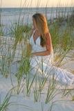 Braut, die auf Sand sitzt Lizenzfreie Stockbilder