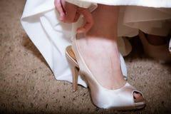 Braut, die auf Schuh sich setzt Stockfotografie