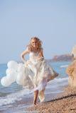 Braut, die auf Strand läuft Stockfoto