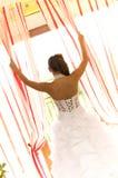 Braut, die aus Fenster heraus schaut Stockfotografie