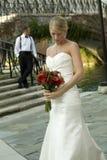Braut, die Blumen mit Bräutigam betrachtet Stockfotografie