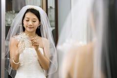 Braut, die Blumenstrauß betrachtet. lizenzfreies stockfoto