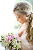 Braut, die Blumenstrauß betrachtet Stockfoto