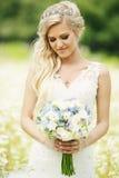 Braut, die Blumenstrauß betrachtet Lizenzfreie Stockbilder