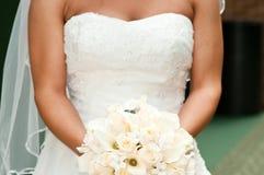 Braut, die Blumenstrauß mit Eheringen anhält. Lizenzfreie Stockbilder