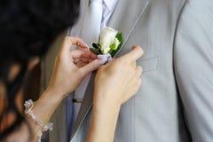 Braut, die Boutonniere des Bräutigams justiert Stockbilder