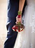 Braut, die Bräutigam umarmt und Hochzeitsblumenstrauß hält Stockfotografie