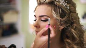 Braut, die Brauenfarbe an Augenbrauen mit brauner Bürste gelangt Berufsmake-up für Frau mit gesunder junger Gesichtshaut stock footage