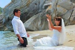 Braut, die Bräutigam mit Meerwasser spritzt Stockfotos