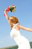 Braut, die bunten Blumenstrauß wellenartig bewegt lizenzfreies stockbild