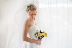 Braut, die das Fenster mit Blumen in ihrer Hand bereitsteht Lizenzfreies Stockfoto