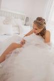 Braut, die das Setzen auf Strumpfband kleidet Stockfotografie