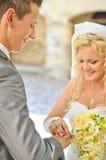 Braut, die dem Bräutigam Ring gibt Stockfoto