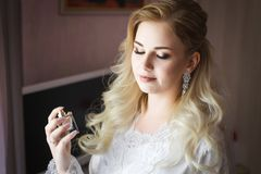 Braut, die in den Händen eine Flasche Luxusparfüm hält Stockbilder