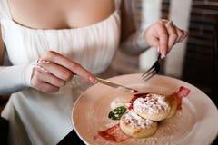 Braut, die in den Pfannkuchen eines Cafés isst lizenzfreie stockbilder