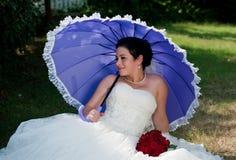 Braut, die in der Hand Regenschirm und rote Rosen boquet hält Stockfotos