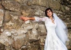 Braut, die an der Steinwand steht Stockfotos