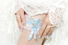 Braut, die ein Strumpfband mit blauem Farbband setzt Lizenzfreie Stockfotos