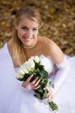 Braut, die in einem Park sitzt Lizenzfreie Stockfotografie