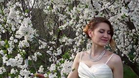 Braut, die in einem schönen blühenden Frühlingsgarten steht stock video footage