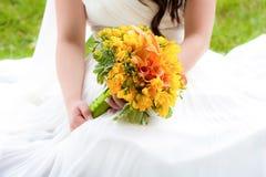 Braut, die einen Blumenstrauß anhält Stockbilder