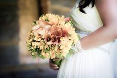 Braut, die einen Blumenstrauß anhält Lizenzfreies Stockfoto