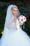 Braut, die einen Blumenstrauß der Hand anhält Lizenzfreies Stockfoto