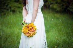 Braut, die einen Blumenstrauß hält Lizenzfreies Stockfoto