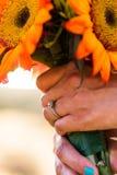 Braut, die einen Blumenstrauß von bunten Sonnenblumen hält Lizenzfreies Stockfoto