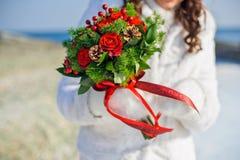 Braut, die einen Blumenstrauß von roten Rosen und von Kiefernkegeln hält Lizenzfreies Stockfoto