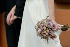 Braut, die einen Hochzeitsblumenstrauß anhält Lizenzfreies Stockbild