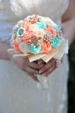 Braut, die einen Hochzeitsblumenstrauß anhält Lizenzfreie Stockbilder