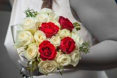 Braut, die einen Hochzeitsblumenstrauß der Rosen anhält Lizenzfreies Stockbild