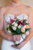 Braut, die einen Hochzeitsblumenstrauß von rosa Rosen hält Stockfotografie