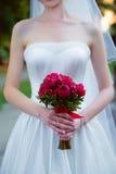 Braut, die einen Hochzeitsblumenstrauß von roten Rosen hält Lizenzfreie Stockbilder