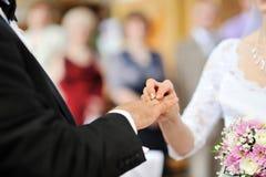 Braut, die einen Hochzeitsring auf Finger des Bräutigams setzt Lizenzfreies Stockfoto