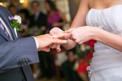 Braut, die einen Hochzeitsring auf Finger des Bräutigams setzt Stockfotografie