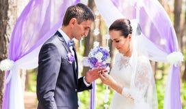 Braut, die einen Hochzeitsring auf Finger des Bräutigams setzt Die Braut mit einer Blume Lizenzfreie Stockfotos