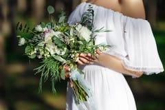 Braut, die einen schönen üppigen Hochzeitsblumenstrauß hält Stockbild