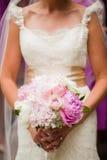 Braut, die einen schönen Blumenstrauß der Blumen anhält Stockfotos
