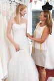 Braut, die für Hochzeits-Kleid vom Geschäftsinhaber gepasst wird Lizenzfreie Stockfotos