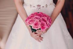 Braut, die hellen Hochzeitsblumenstrauß der rosa Rosennahaufnahme hält Lizenzfreie Stockfotos