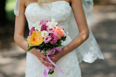 Braut, die Hochzeits-Blumenstrauß mit orange weißen und rosa Blumen hält Lizenzfreies Stockfoto