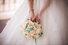 Braut, die Hochzeitsblumenstrauß von den weißen Rosen hält Stockfotos