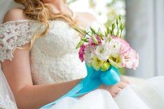 Braut, die Hochzeitsblumenstraußabschluß hochhält Lizenzfreies Stockfoto