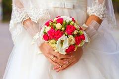 Braut, die Hochzeitsblumenstraußabschluß hochhält Lizenzfreie Stockfotos
