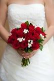 Braut, die ihr rosafarbenen Blumenstrauß zeigt Lizenzfreies Stockfoto
