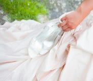 Braut, die ihre Schuhe behandelt Lizenzfreie Stockbilder