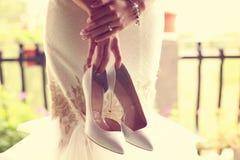 Braut, die ihre Schuhe hält Stockfoto